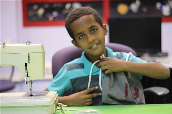 נער יושב ליד מכונת תפירה
